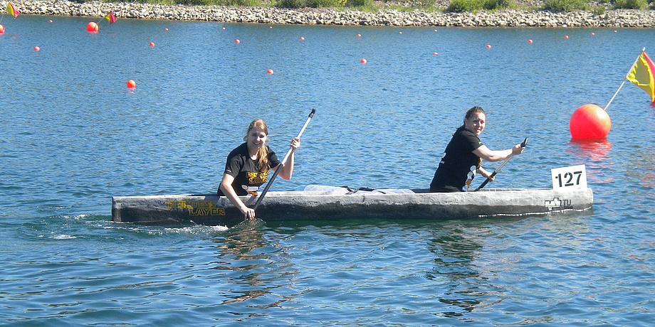 Ein See ist zu sehen auf dem ein graues, längliches Kanu fährt. In ihm sitzen zwei junge Frauen.