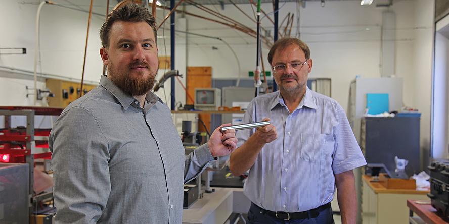 Peter Pichler und Gernot Pottlacher stehen in einem Labor und halten einen Eisenstab in der Hand.