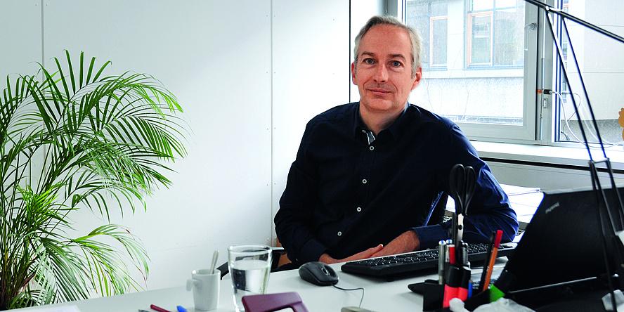 Ein Mann mit blauen Augen, grau meliertem Haar und dunklem Hemd sitzt an seinem Schreibtisch zwischen einem großen Fenster und einer Zimmerpalme.