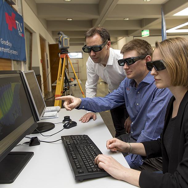 Zwei Studierende und ein Lehrender blicken durch 3D-Brillen auf eine Bildschirm mit einer Simulation.