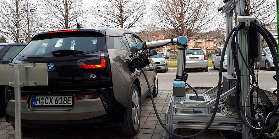 Ein blaues Elektrofahrzeug wird mittels des Roboters aufgeladen. Der Arm des Roboters steckt in der Steckdose des Fahrzeugs.