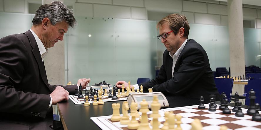 Zwei Männer sitzen an einem Tisch und spielen Schach. Beide schauen sehr konzentriert.