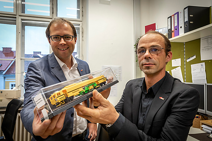 Two TU Graz researchers with a model of a tamping machine in their hands
