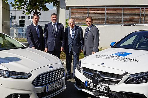 vier Männer posieren mit zwei selbstfahrenden Autos