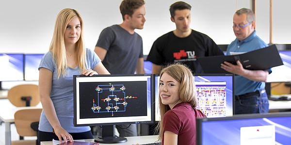 Studierende sitzen und stehen rund um einen Computerbildschirm.