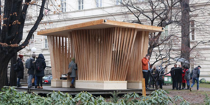 """Aufnahme des Holzpavillons """"Twist"""" mit neugierigen Besucherinnen und Besuchern im Innenhof des Campus Alte Technik."""