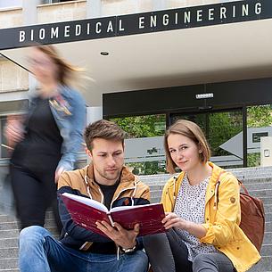 """Zwei Studierende sitzen auf Stufen vor einem Gebäude mit der Aufschrift """"Biomedical Engineering""""."""