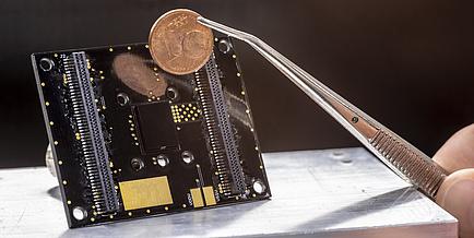 Sensor im Vordergrund eine Pinzette mit Ein-Cent-Münze