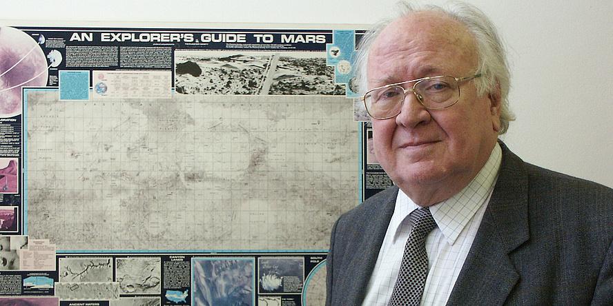 Willibald Rielder posiert  vor einem Plakat mit Weltraumbezug