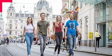 Four young people walk through an inner city street.