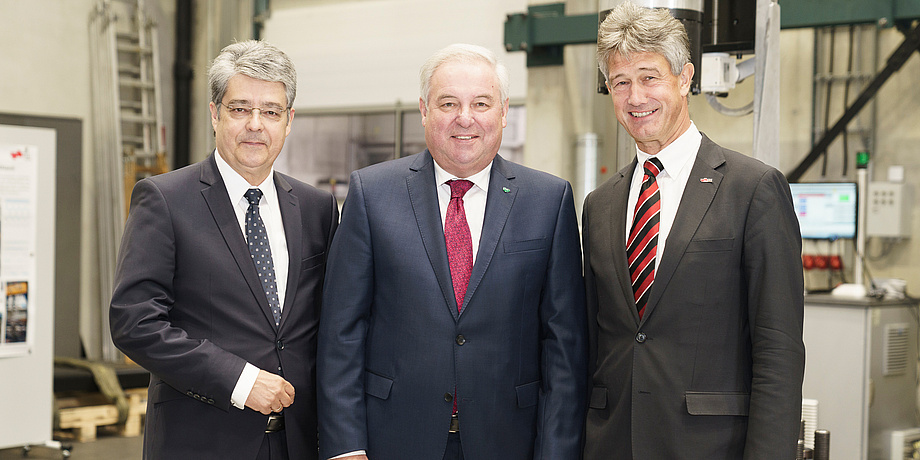 Siemens Austria CEO Wolfgang Hesoun, state governor Hermann Schützenhöfer and TU Graz Rector Harald Kainz are standing in a row. In the background, you can see the structural durability laboratory 'Fatigue Testing Laboratory'