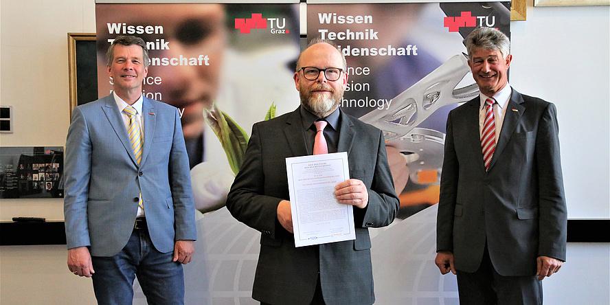 Drei Männer blicken in die Kamera und der Mann in der MItte hält eine kleine Urkunde in der Hand