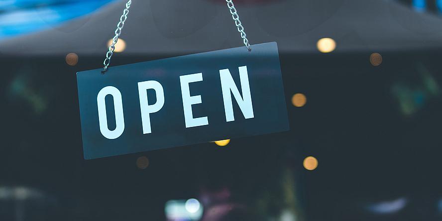 """Schild an einer Tür mit dem Schriftzug """"Open"""""""