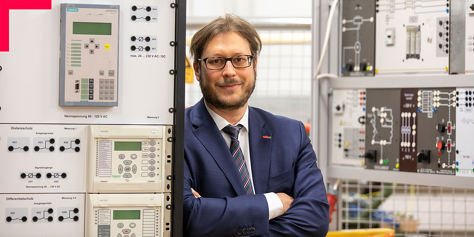 Man with beard and glasses in an electrical engineering laboratory, leaning against a piece of equipment
