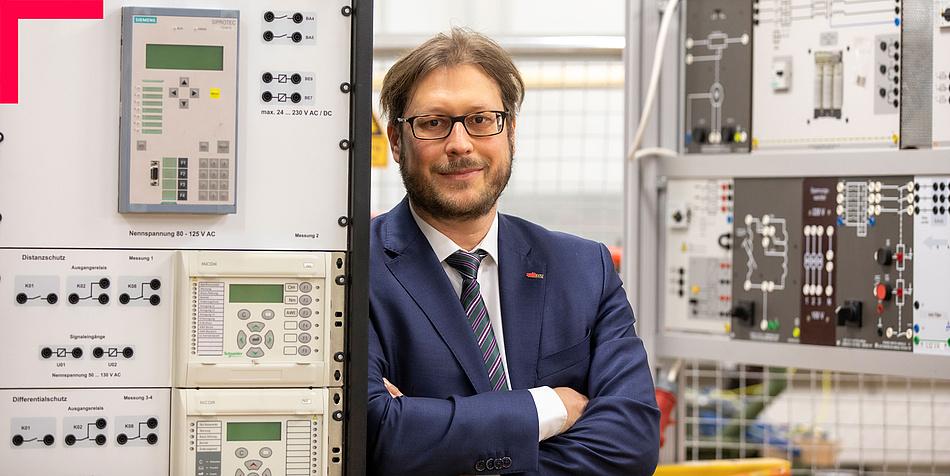 Mann mit Bart und Brille in einem elektrotechnischen Labor, an eine Anlage gelehnt