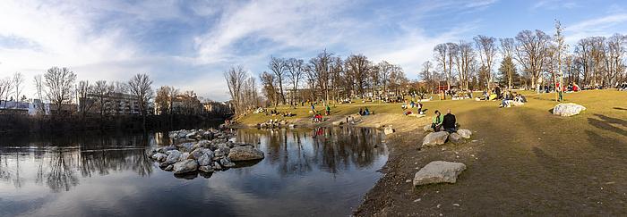 Park mit vielen verweilenden Menschen an einem Fluss im frühen Frühling.