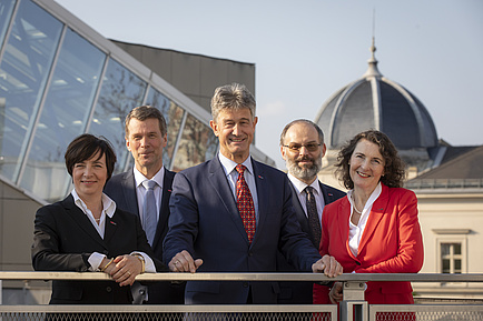 The team of two women and three men is standing in the sun - in the background the dome of a building on the campus Alte Technik.