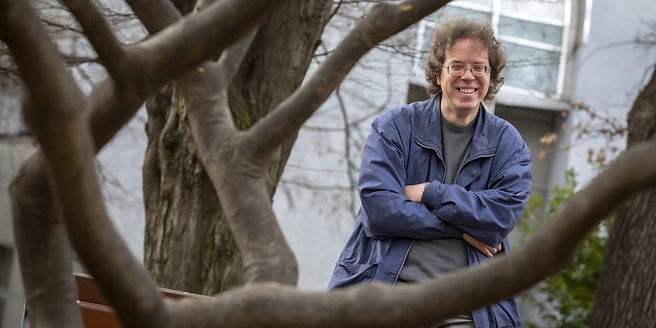 Ein Mann steht mit überkreuzten Armen an einem Baum und lacht.