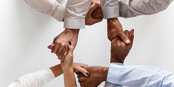 Four people shake hands, only the hands are seen in the picture. They form a square.