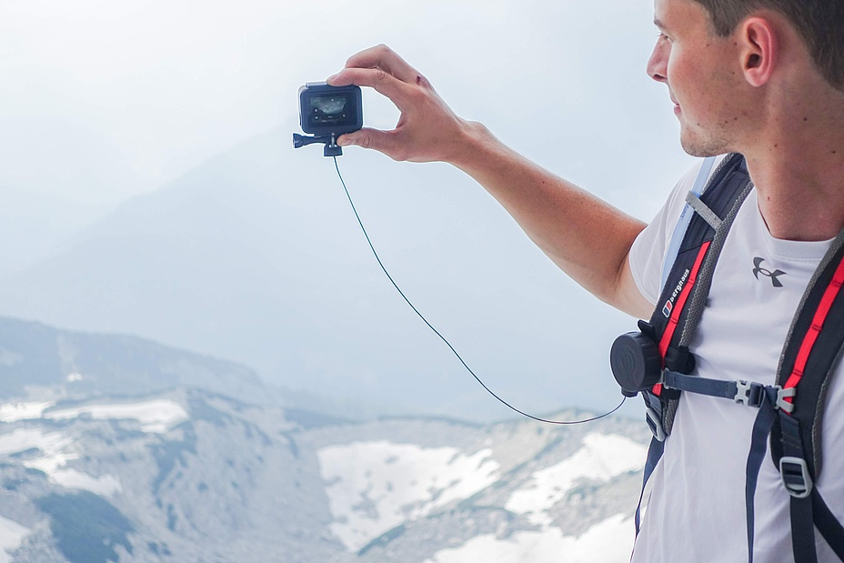 Young man shoots a snowy landscape with an action camera secured by a rope pull.