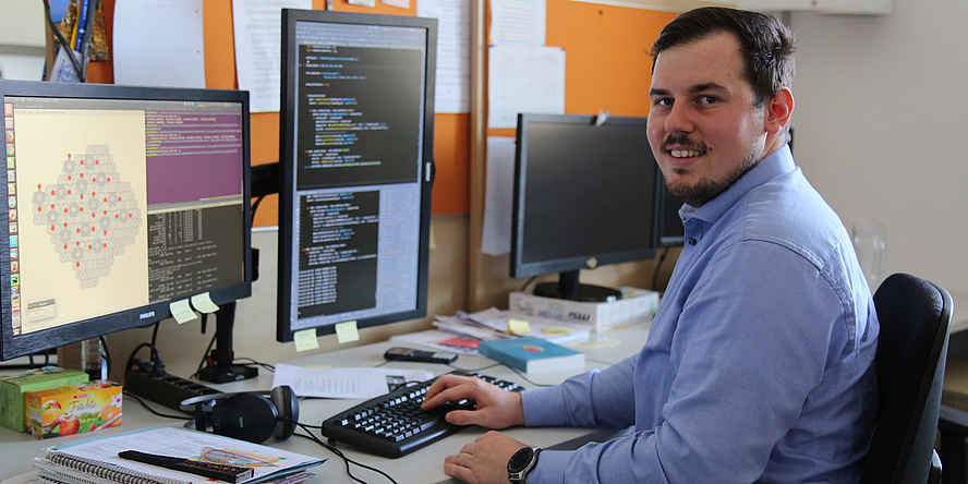 A young man is sitting at a desk. He wears a blue shirt, short brown hair and a short beard. His right hand touches the keybord. On the computerscreen there is a grey grafic with red elements.