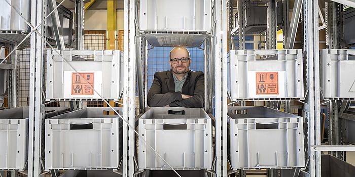 Christian Landschützer steht hinter einem Regal, in dem Kisten gestapelt sind. Er blickt durch einen Spalt im Regal.