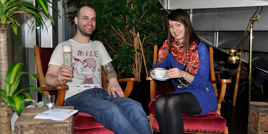 A man with a beard, a tattoo on his arm and a beer in his hand as well as a woman with medium-length brown hair, purple long-sleeved sweater and red cloth and a cup of coffee in hand sit on comfortable chairs covered with red velvet armchairs, green plants behind them.