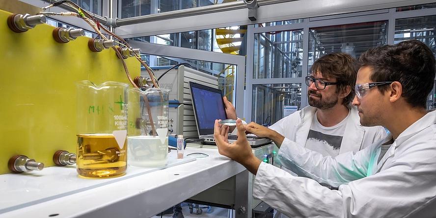 Zwei Forscher der TU Graz vor einem Versuchsaufbau mit Redox Flow Elektrolyte