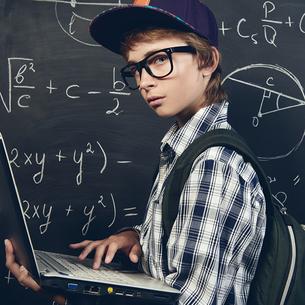 Ein Schüler mit Notebook in der Hand steht vor einer Tafel