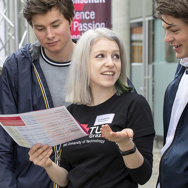 Eine Studentin im Gespräch mit zwei Schülern.