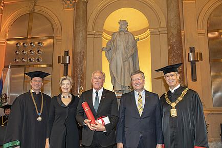 Fünf Menschen stehen vor der Statue von Kaiser Joseph II., die äußeren beiden Herren tragen einen Talar, jener in der Mitte hält eine rote Urkundenrolle in Händen.