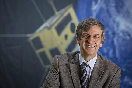 Otto Koudelka, Forscher an der TU Graz, vor einem Bild des Nanosatelliten TUGSAT-1.