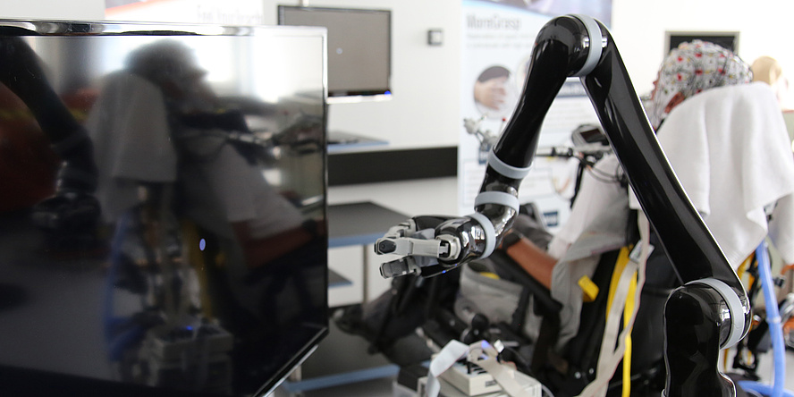 Robotischer Arm vor einem Fernseher, im Hintergrund Proband mit EEG-Haube
