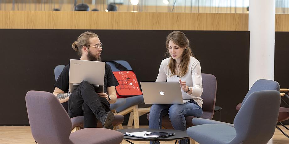 Ein junger Mann und eine junge Frau, beide mit Laptop und im Gespräch miteinander