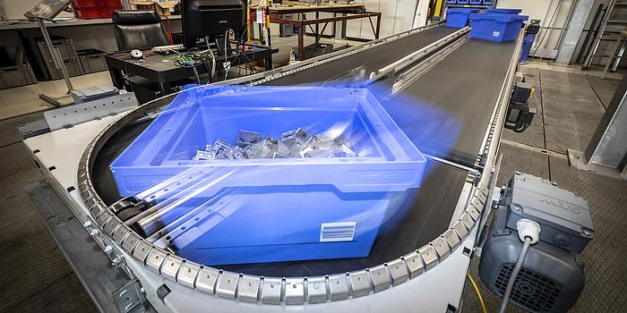 Eine Paketbox fört auf einem Förderband im Kreis.