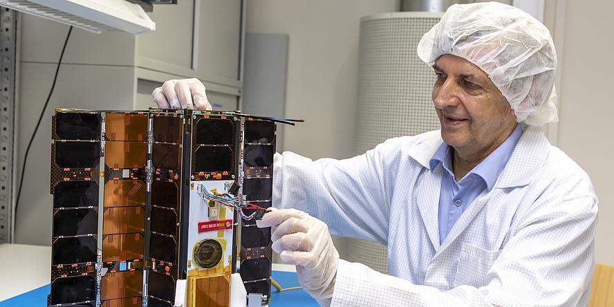 Ein Mann mit weißem Labormantel und weißem Häubchen über den Haaren sitzt an einem Schreibitsch und arbeitet an einem Satelliten. Der Satellit steht aufgeklappt mit den schwarzen Solarpanelen nach vorne auf dem Tisch.