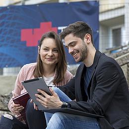 Eine junge Frau und ein junger Mann mit Tablet und Schreibblock.
