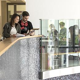 Eine Frau und ein Mann mit Tablet und Unterlagen in einem Stiegenhaus.