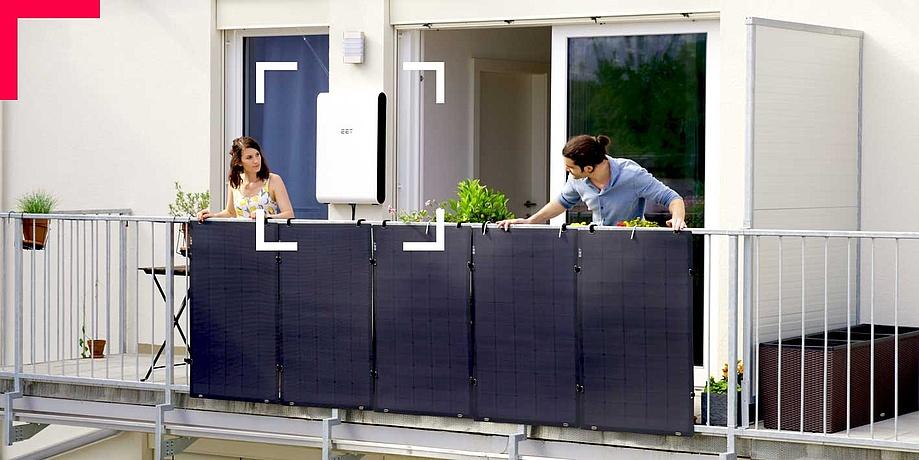Mann und Frau beugen sich über ein Balkongeländer mit Solarpanelen.