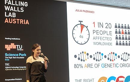 Eine junge Frau mit Mikrophon in der Hand steht auf einer Bühne und präsenteirt. Im Hintergrund ist eine Grafik eingeblendet