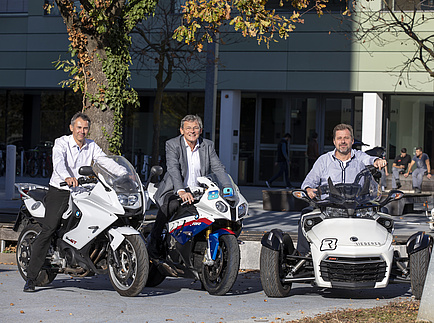 Three men sit on Personal Mobility vehicles - two motorcycles and a Powersport device
