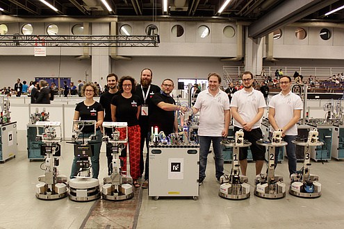 The world champion team GRIPS consisting of two women and three men in black T-shirts and the vice world champion team PYRO consisting of three men in white T-shirts posing with their sehcs robots in a production hall.
