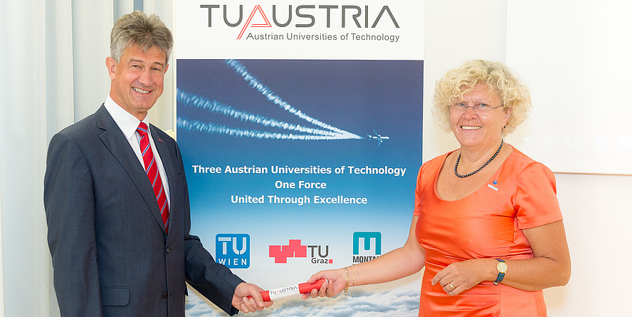 Rektor Harald Kainz und Rektorin Sabine Seidler mit einem rot-weiß-roten Staffelholz vor einem TU Austria Roll-up