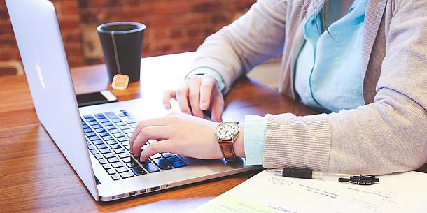 Eine Person tippt auf einer Laptop-Tastatur. Im Vordergrund ist ein Kalender, im Hintergrund sind ein Handy und eine Tasse Tee auf dem Schreibtisch zu sehen.