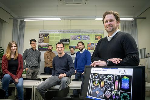 Gruppe von Menschen in Büro, rechts Bildschirm mit Abbildungen von Nanostrukturen, hinten ein Poster zu Nanoanalytik