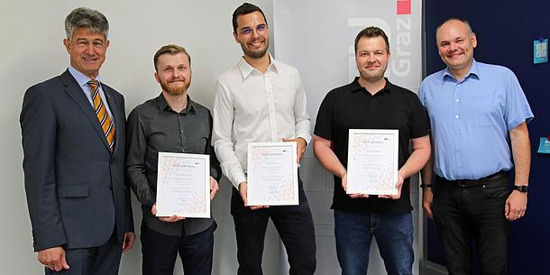 Drei Lehrende der TU Graz zeigen Urkunden in die Kamera. Links neben ihnen steht Rektor Harald Kainz, rechts neben ihnen Martin Ebner.