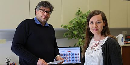 Ein Mann im schwarzen Pullover und eine Frau in weißer Bluse schauen in die Kamera. Hinter ihnen befindet sich ein Computerbildschirm mit bunten Abbildungen.