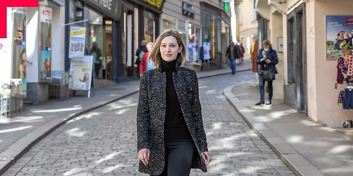 Junge Frau, groß im Bild, geht durch belebte Einkaufsstraße.
