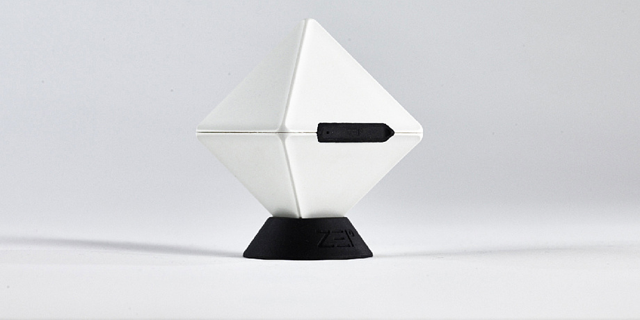 A white cube standing on a corner in a black stand. In the front is a black, elongated opening in the cube.