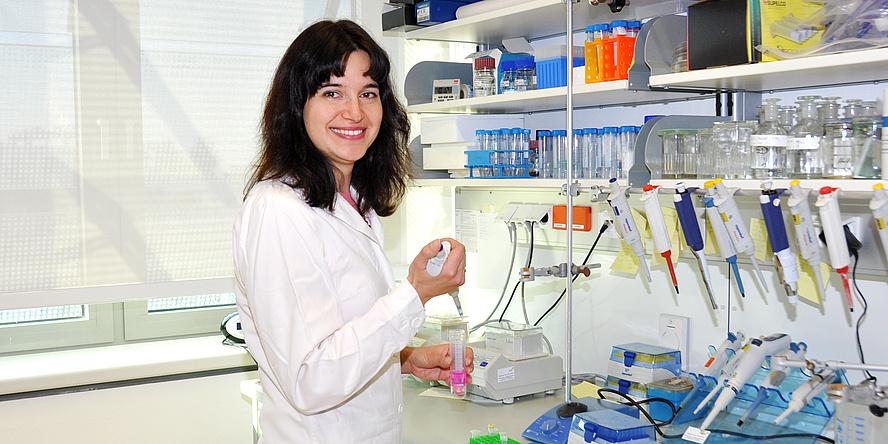Kateryna Lypetska steht im Labor, in den Händen hält sie eine Pipette und eine Eprouvette.